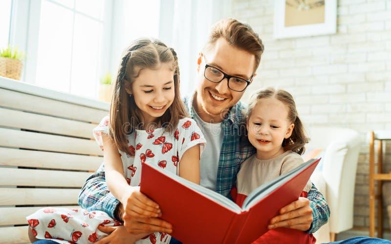 Padre que lee un libro a sus hijas imágenes de archivo libres de regalías