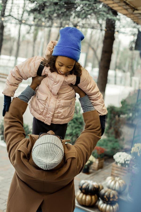 Padre que lleva la capa marrón que detiene a su niña en sus manos fotografía de archivo libre de regalías