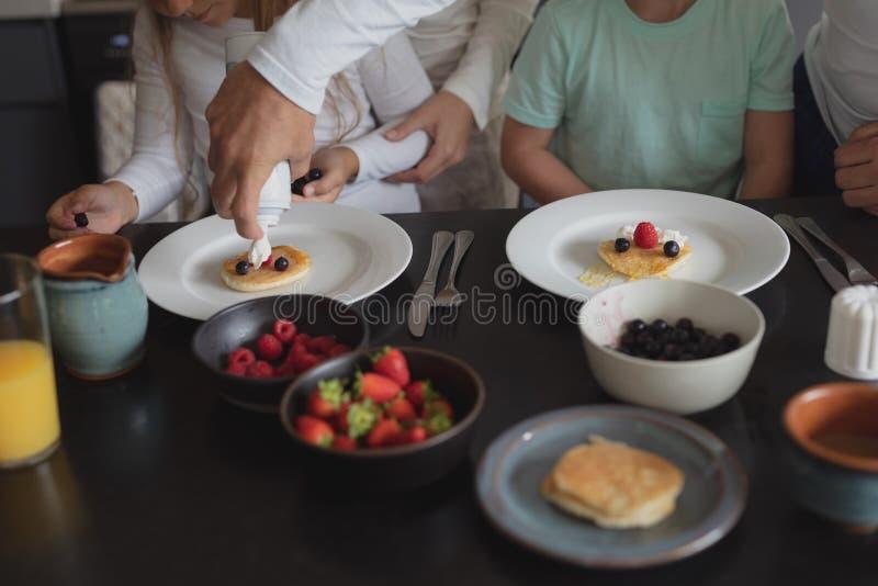 Padre que pone la crema en la crepe en la mesa de comedor foto de archivo libre de regalías