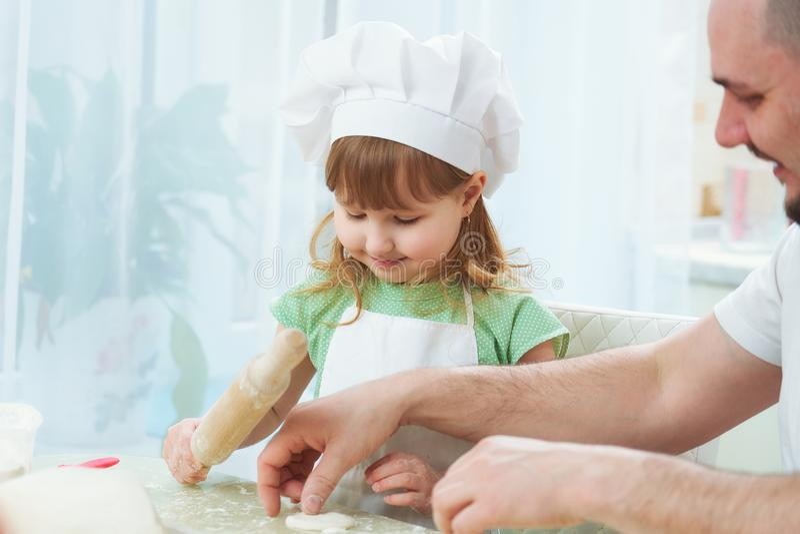 Padre que prepara la comida con mi hija un hombre enseña a un niño a cocinar el proceso de cocinar en una cocina brillante la coc fotos de archivo libres de regalías