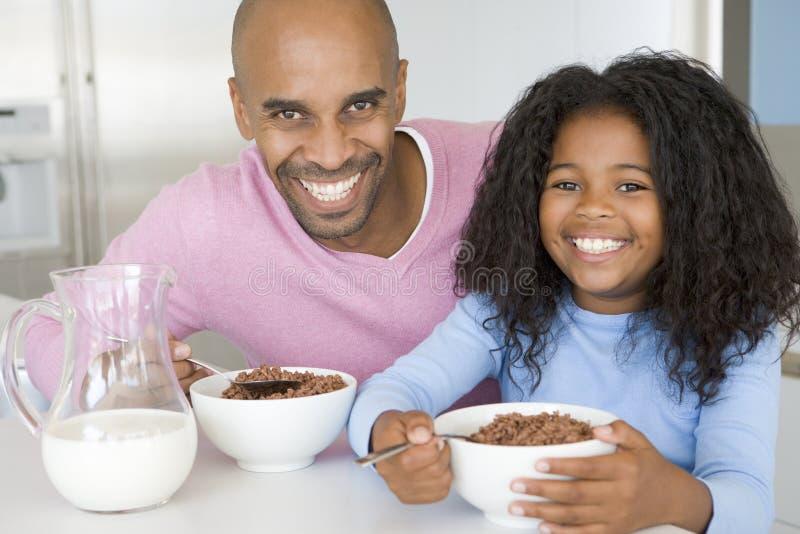 Padre que se sienta con el desayuno de Eatting de la hija imágenes de archivo libres de regalías