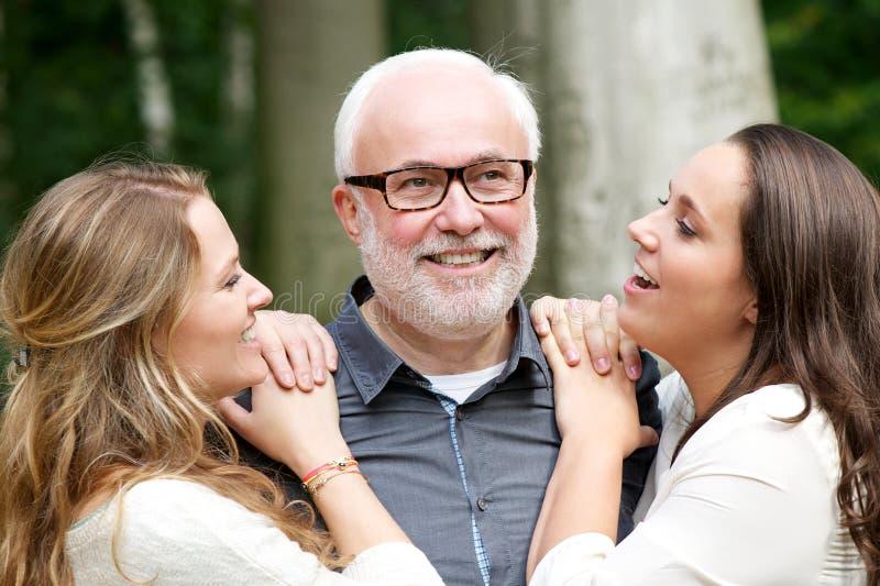 Padre que sonríe con sus dos hijas al aire libre imagen de archivo libre de regalías