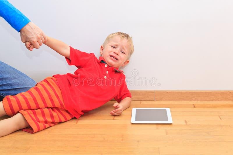Padre que tira del niño de la almohadilla táctil foto de archivo