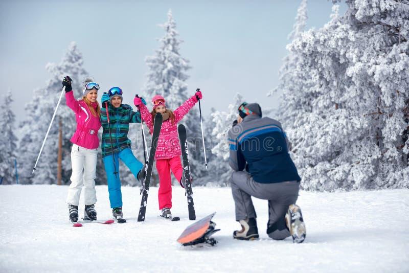 Padre que toma la imagen de la familia en snowoutdoor en día soleado foto de archivo libre de regalías