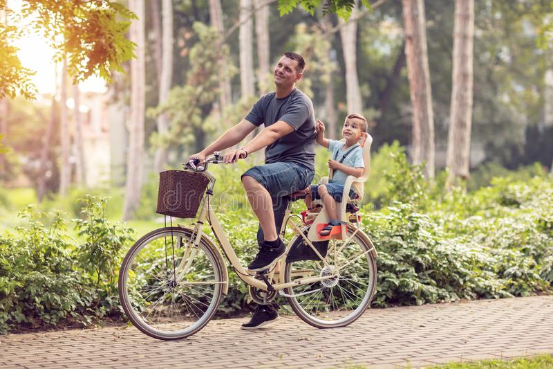 Padre sonriente con el muchacho en las bicicletas que se divierten en parque Familia s imagen de archivo libre de regalías