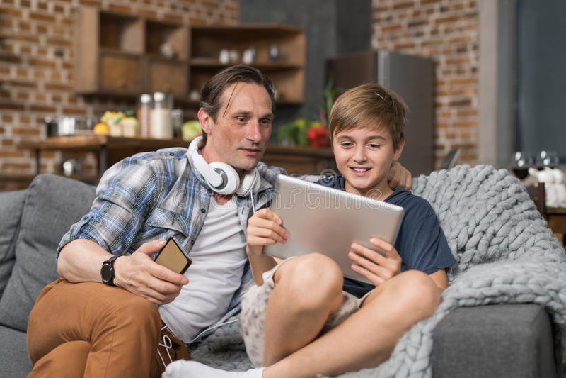 Padre sonriente feliz And Son Sitting en la tableta del uso del sofá, padre que gasta al niño del tiempo foto de archivo