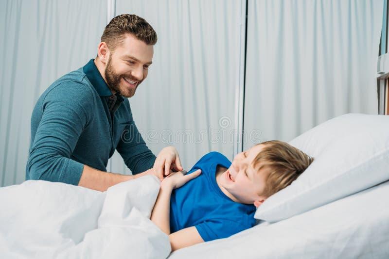 Padre sonriente que juega con el niño pequeño enfermo que miente en cama de hospital foto de archivo