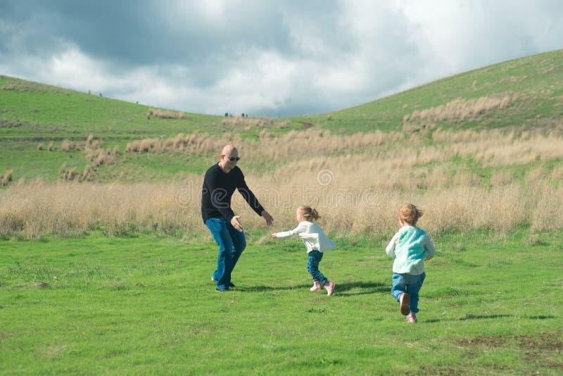 Padre sonriente que juega con sus dos hijas de risa en el parque imágenes de archivo libres de regalías