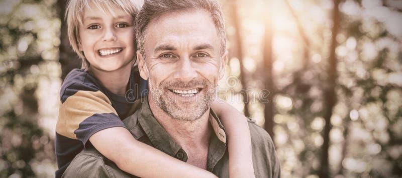 Padre sonriente que lleva a cuestas al hijo en bosque fotografía de archivo