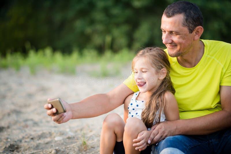 Padre sonriente que toma el selfie con la hija joven al aire libre imagen de archivo