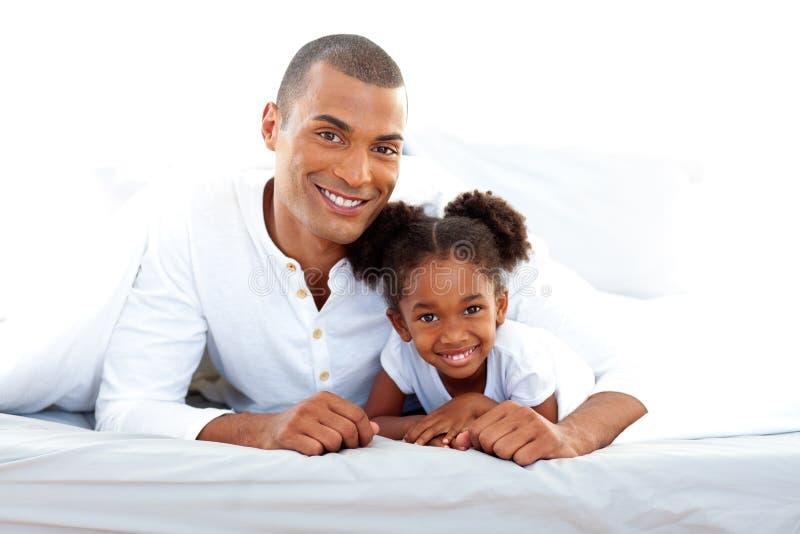 Padre sonriente y su hija que se divierten fotografía de archivo