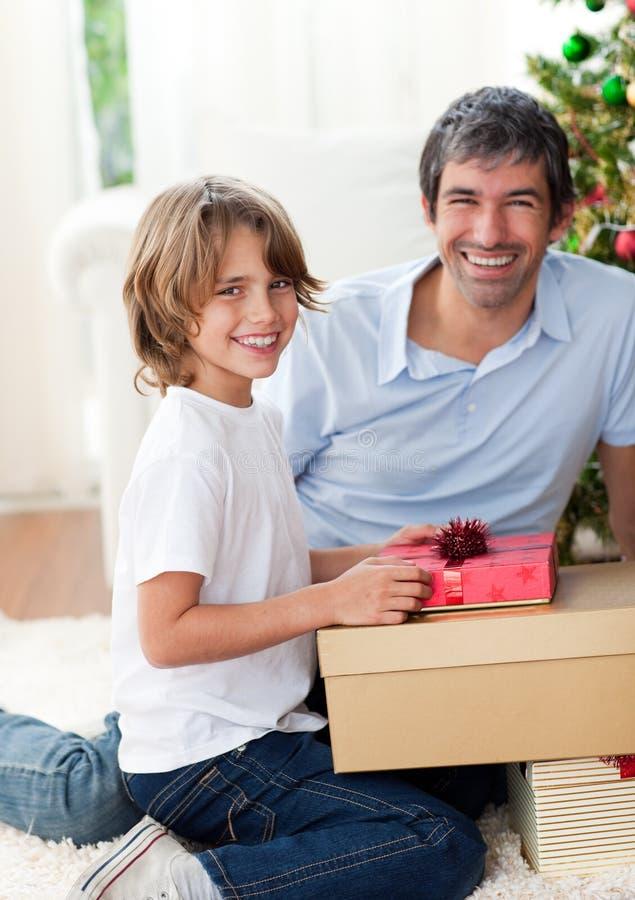 Padre sonriente y sus regalos de la Navidad de la apertura del hijo imágenes de archivo libres de regalías
