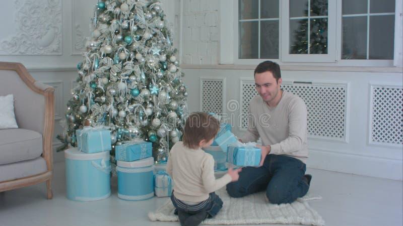 Padre sonriente y sus regalos de Navidad de la abertura del hijo en la sala de estar foto de archivo