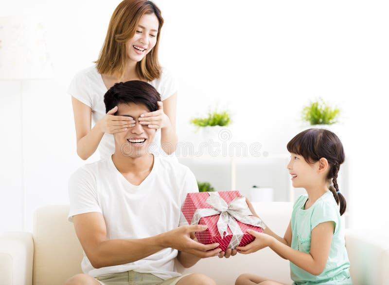 Padre sorpreso che riceve il contenitore di regalo dalla moglie e dalla figlia fotografie stock