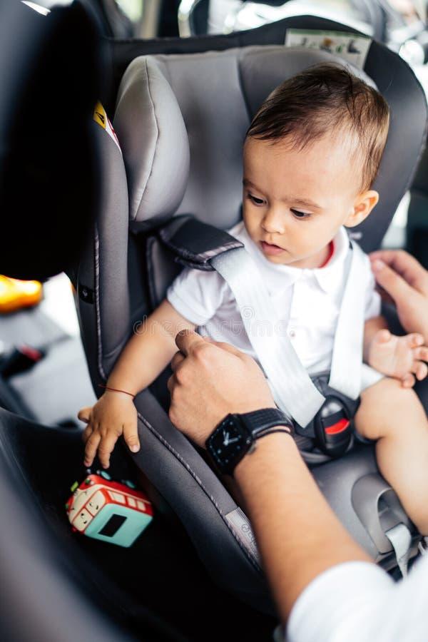 Padre sorridente che mette bambino nel sedile del bambino, cintura di sicurezza di fissaggio - trasporto della famiglia, concetto immagini stock libere da diritti