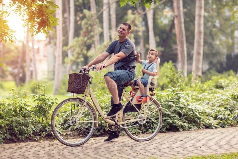 Padre sorridente con il ragazzo sulle biciclette divertendosi nel parco Famiglia s immagine stock libera da diritti