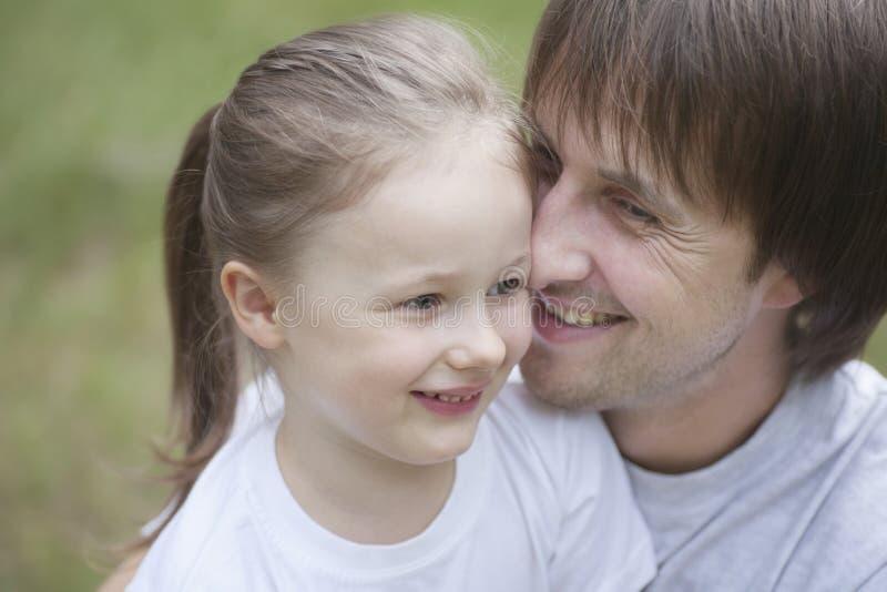 Padre sorridente Cuddling Daughter fotografia stock