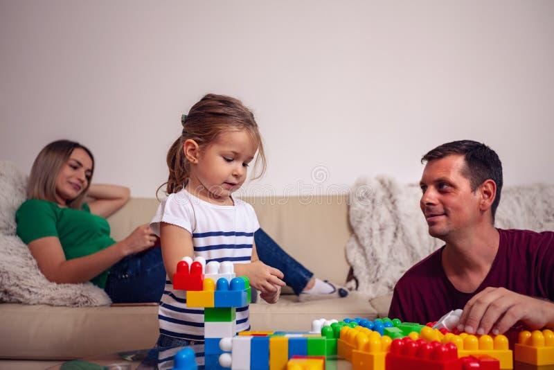 Padre sorridente e piccola figlia che giocano insieme con i cubi a immagini stock