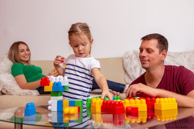 Padre sorridente e piccola figlia che giocano insieme con i cubi a casa immagini stock libere da diritti
