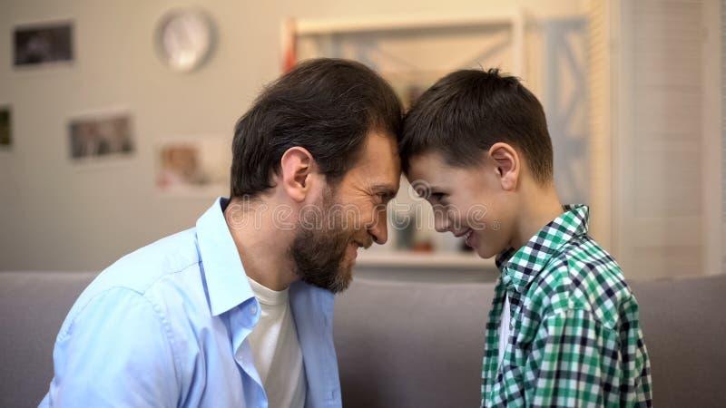 Padre sorridente e piccolo figlio che toccano le fronti, relazioni fiduciose, amici fotografia stock
