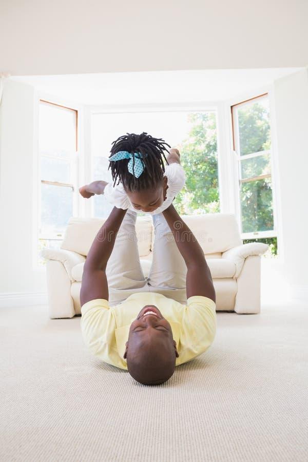 Padre sorridente felice che tiene sua figlia fotografie stock libere da diritti
