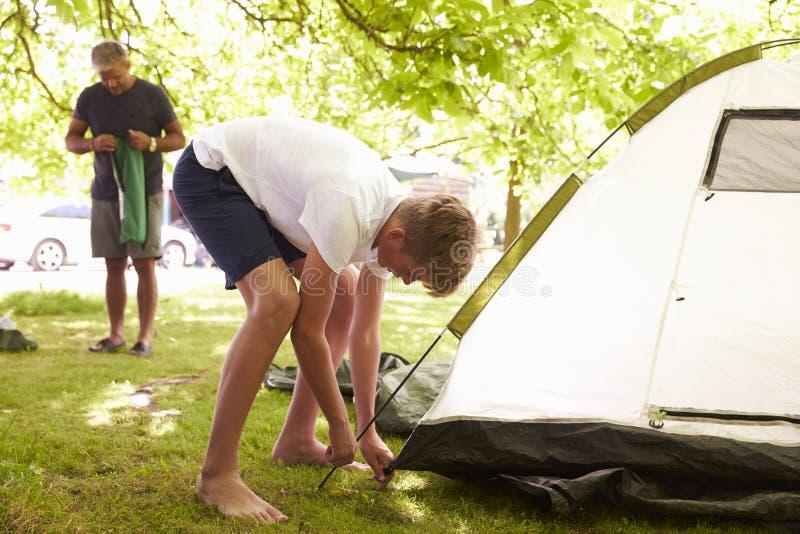 Padre And Teenage Son che mette sulla tenda sul viaggio di campeggio immagini stock