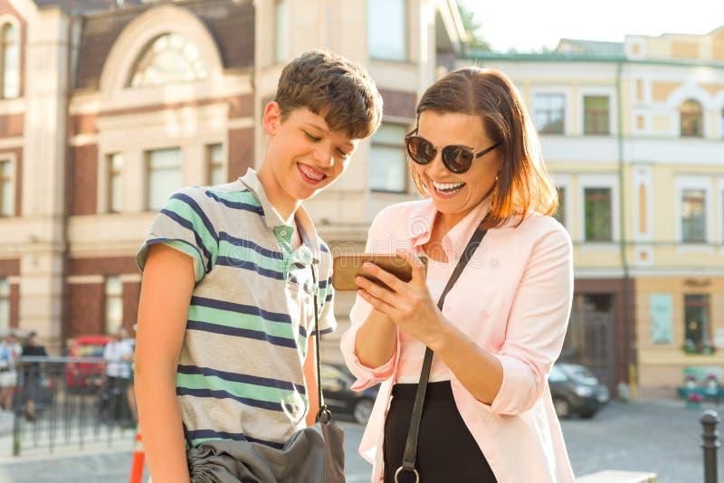 Padre y adolescente, relación La madre y el hijo adolescentes están mirando el teléfono móvil y están riendo, fondo de la calle d imagen de archivo