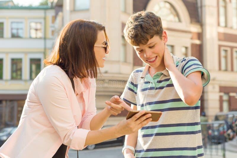 Padre y adolescente, relaci?n Se desconcierta la madre muestra a su hijo algo en el teléfono móvil, muchacho, sonrisa, celebrando imagen de archivo