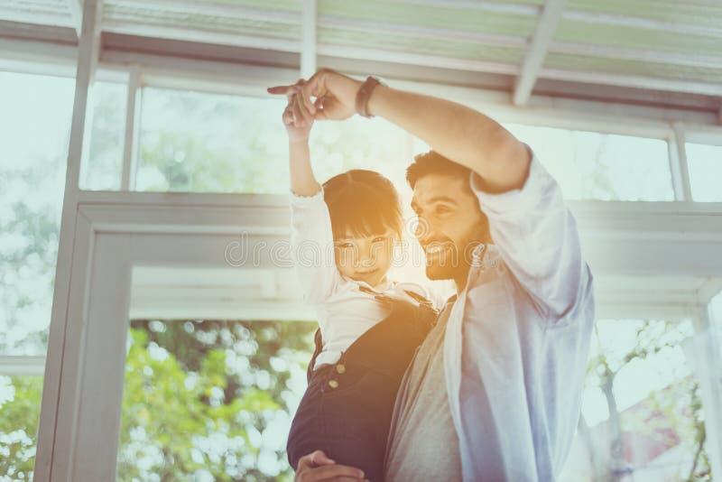 Padre y baile joven de la hija y el jugar, riendo y divertido junto en casa, familia cariñosa feliz fotografía de archivo