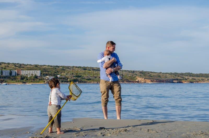 Padre y bebé y niño que juegan en la playa arenosa foto de archivo libre de regalías