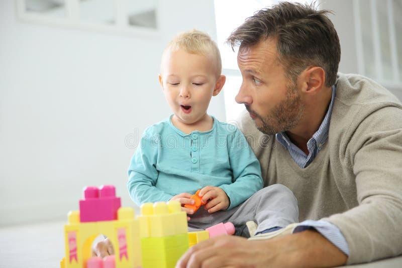 Padre y bebé que juegan así como bloques del juguete imagenes de archivo