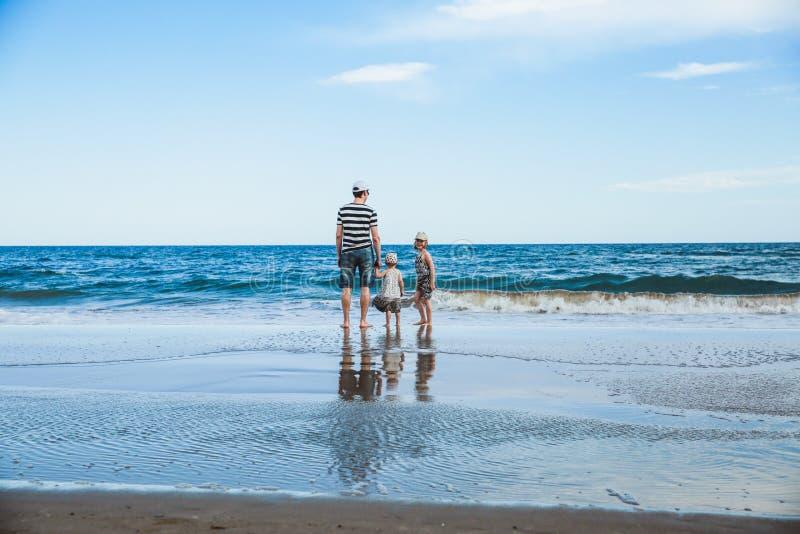 padre y dos hijas que se colocan en la playa fotografía de archivo