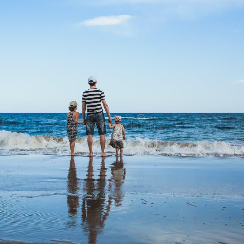 padre y dos hijas que se colocan en la playa imagen de archivo