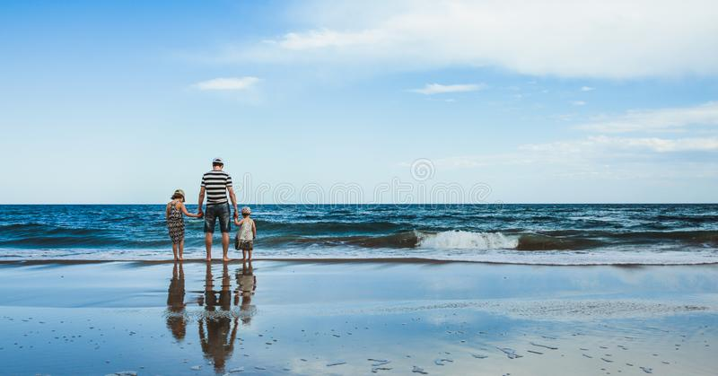 padre y dos hijas que se colocan en la playa imagenes de archivo
