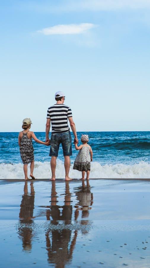 padre y dos hijas que se colocan en la playa fotos de archivo libres de regalías