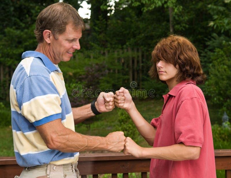 Padre y el puño-topar adolescente del hijo fotografía de archivo