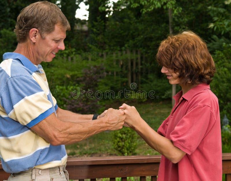 Padre y el puño-topar adolescente del hijo imagen de archivo libre de regalías