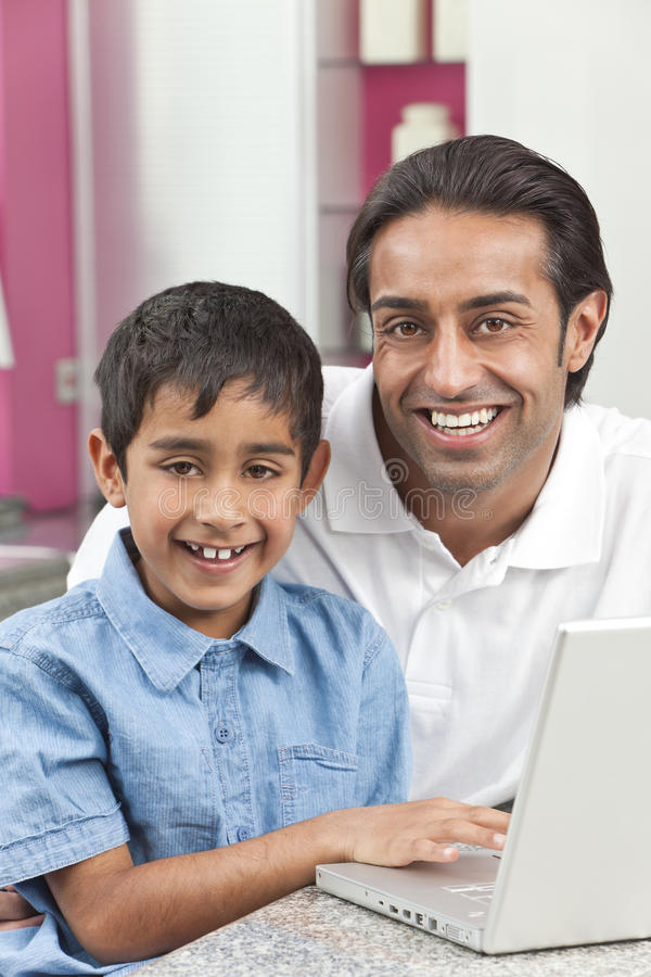 Padre y hijo indios que usa el ordenador portátil en el país imagenes de archivo