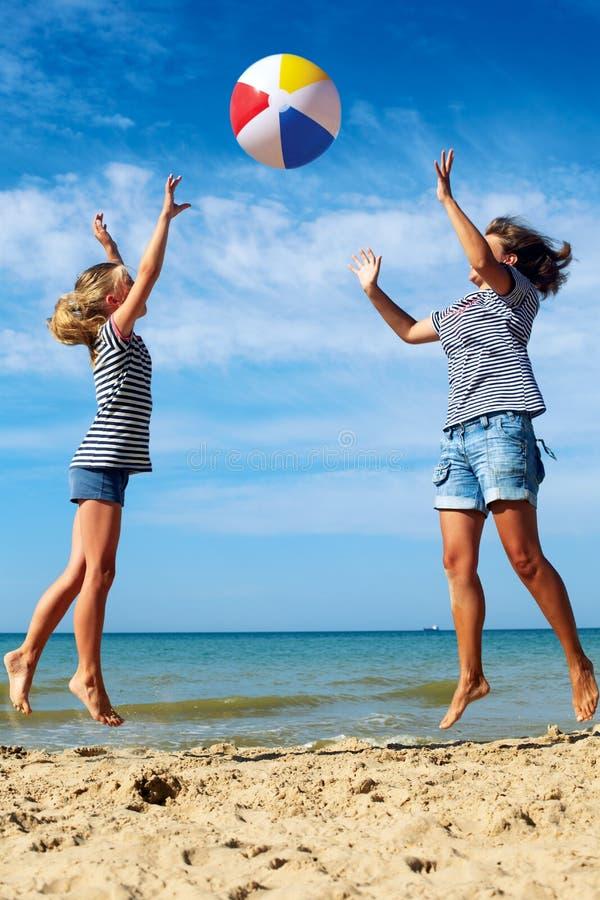 Padre y juego de niños una bola en la costa en un día de verano soleado imagenes de archivo