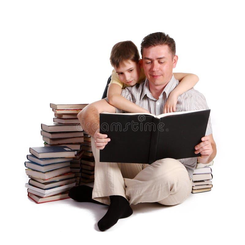 Padre y libros de lectura jovenes del muchacho imágenes de archivo libres de regalías