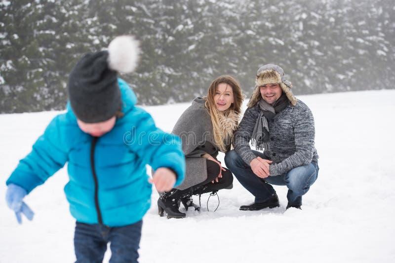 Padre y madre con su hijo, jugando en la nieve foto de archivo libre de regalías