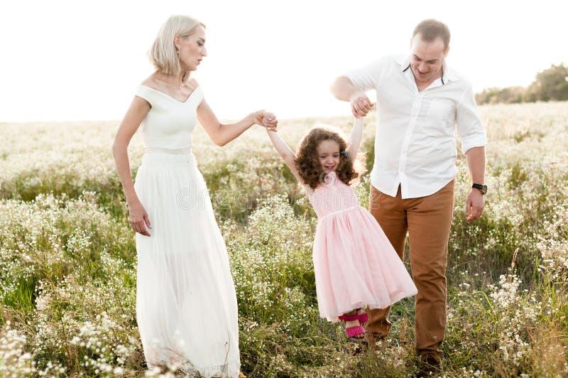 Padre y madre que balancean a una niña imagen de archivo