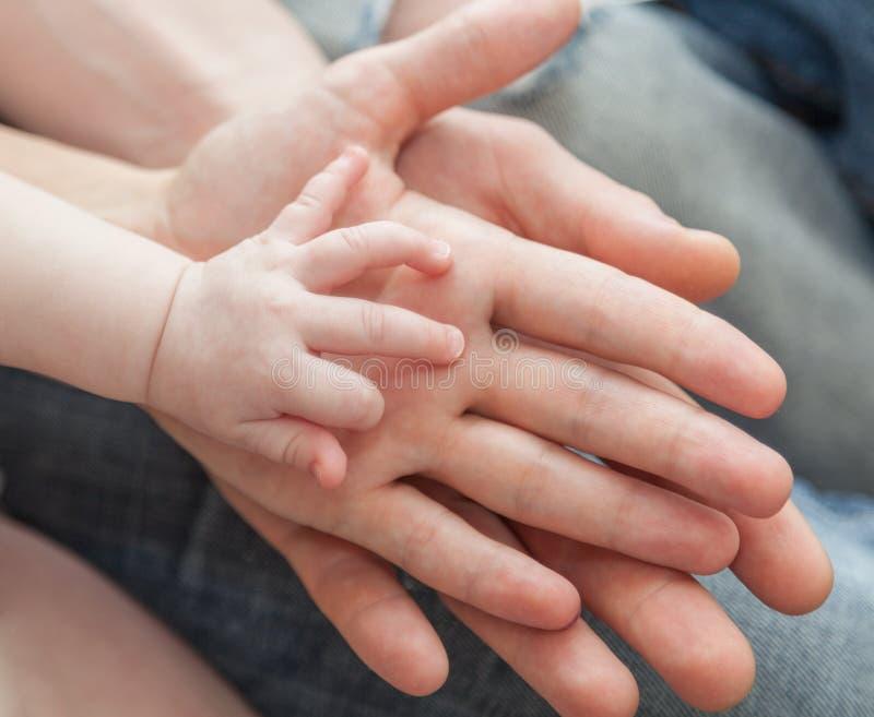 Padre y madre que celebran la mano del niño imágenes de archivo libres de regalías