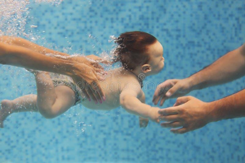 Padre y madre que enseñan al pequeño niño que nada bajo el agua en la piscina foto de archivo libre de regalías