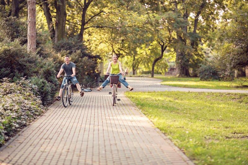 Padre y madre sonrientes con el niño en las bicicletas que se divierten en par foto de archivo libre de regalías