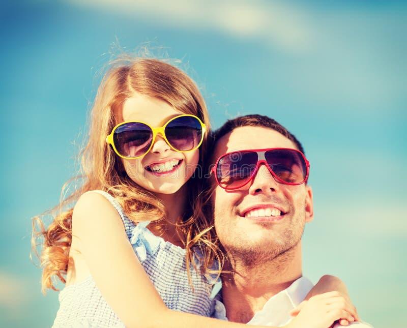 Padre y niño felices en gafas de sol sobre el cielo azul imagenes de archivo