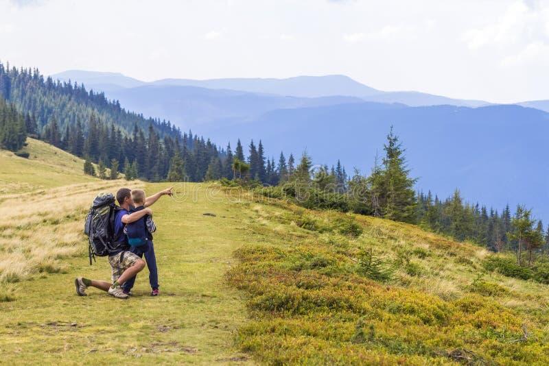 Padre y niño que caminan en montañas escénicas Enjoyin del papá y del hijo imagen de archivo