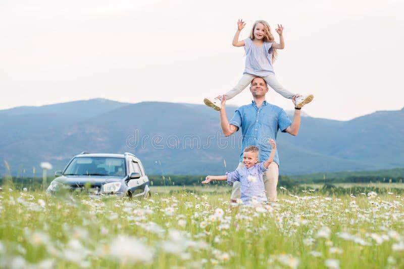 Padre y niños en el coche campo a través que juega en el campo imágenes de archivo libres de regalías