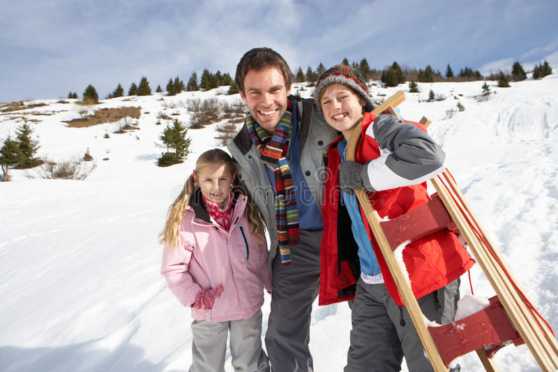 Padre y niños jovenes en nieve con el trineo imagen de archivo