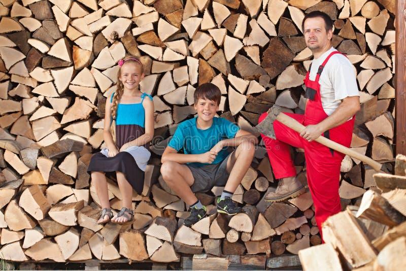 Padre y niños preparados para tajar la leña y para apilarla en un wo fotos de archivo